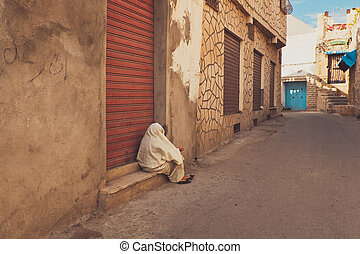 Old woman giving asking alms on the street sitting near...