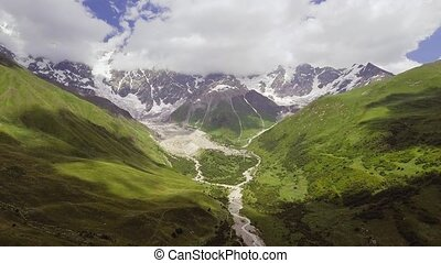 AERIAL.: River in mountain valley at the foot of Mt....