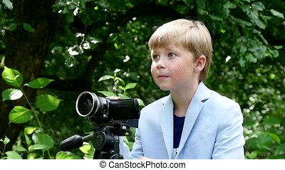 Young boy with video camera shoots film about nature on green park slow motion.