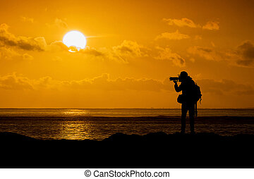 Silhouette of photographer with camera at sunset.