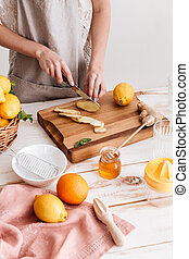 Cropped image of young woman cut the ginger. - Cropped image...