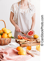 Cropped picture of young woman cut the grapefruit. - Cropped...
