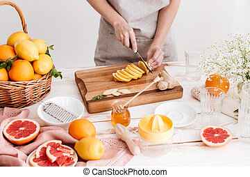 Cropped picture of young woman cut the lemon. - Cropped...