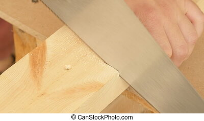 Cutting wood by hand saw - closeup work operation of cutting...