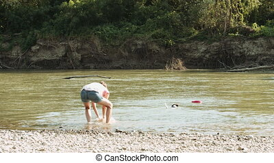 Woman playing with dog near river