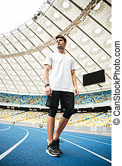 Low angle view of a young sportsman walking on a racetrack...