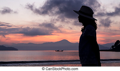 Asian woman silhouette at sunrise ocean pink and orange sky