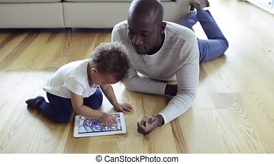 Afro-american father with little daughter with tablet at...
