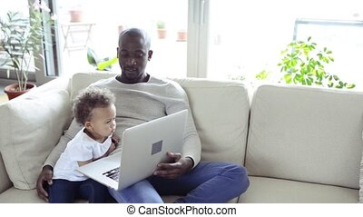 Afro-american father with little daughter at home holding...