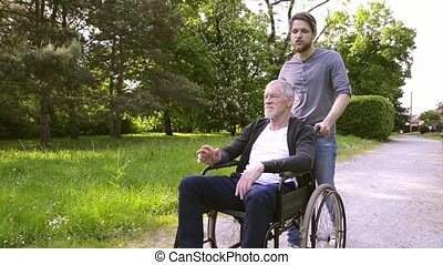 Hipster son walking with disabled father in wheelchair at...