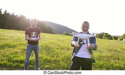 Senior father and his son with drone outdoors. - Senior...
