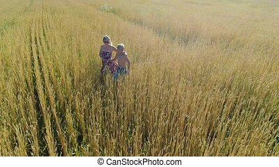 the girl and her baby are walking through a wheat field....