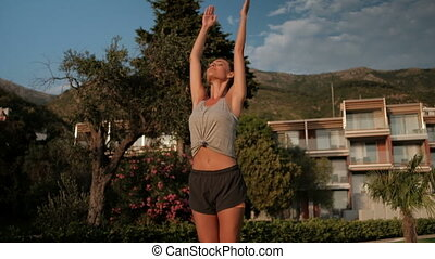 Slender woman raises her arms up and breathe clean air on...