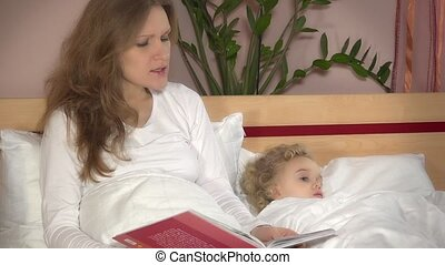 Cute little girl lying in bed while mother woman read tale book