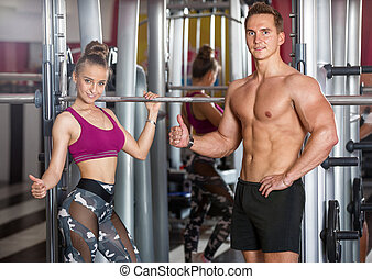 sporty girl and a man posing in the gym near the equipment