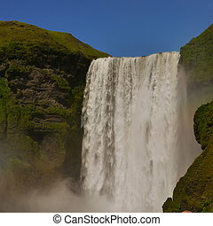 Skogafoss Waterfall with blue sky above, South Iceland