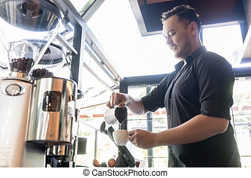 Serious bartender pouring fresh milk into a cup of coffee in a t