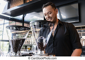Happy young man preparing espresso while working as barista in a