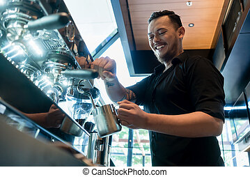 Young cheerful barista preparing coffee at an automatic machine