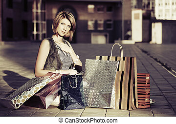 Young fashion woman with shopping bags sitting on the...