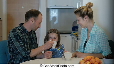 A family of three people drinks a drink and has a cheerful mood.