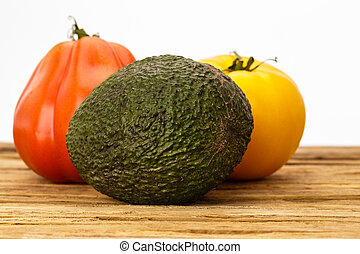 A pair of tomatoes and an avocado grouping with white background