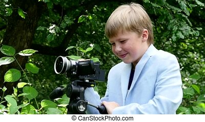 Young boy with video camera on tripod shoots film about nature slow motion.