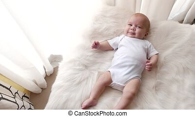 Baby portrait - A cute little baby is looking into the...
