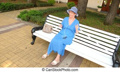 A sweet elderly lady is sitting on a bench in a city park....