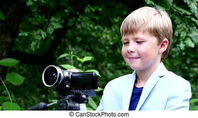 Young boy with video camera on tripod shoots film about nature in green park.