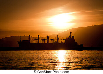 Merchant Ship in the Sunset - A merchant cargo ship...