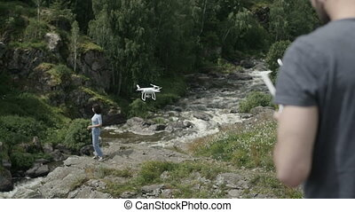 Man with drone and woman on nature