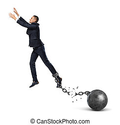 A businessman leaping away from an attached iron ball with a...