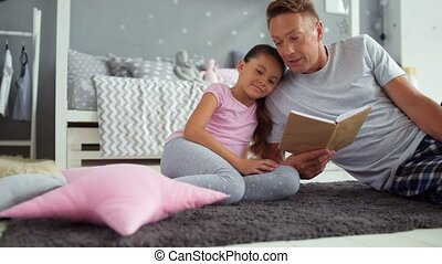 Caring father reading fairy tale for his little daughter -...