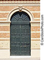 Brick classic building facade with green wooden door. Architecture