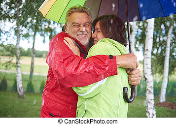 Couple standing and embrancing under umbrella