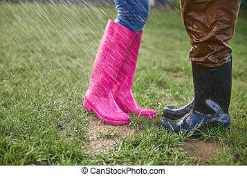 Man and woman in rubber boots outdoors in rainy day