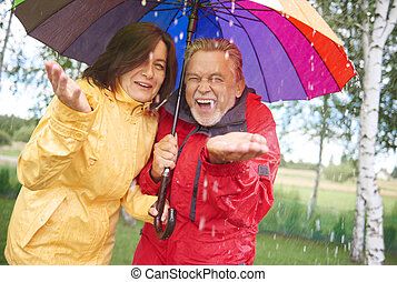 Cheerful couple standing in the autumn rain with umbrella