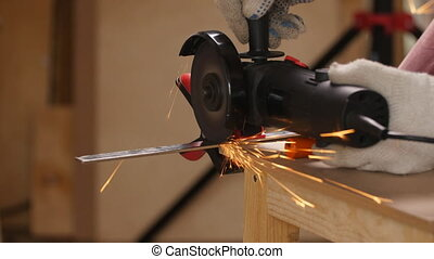 Worker cutting metal with an angle grinder - The worker...