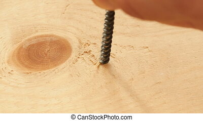 Screwing the screw in a wooden board screw gun