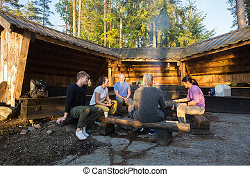 Friends Cooking Food By Shed In Forest