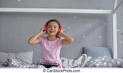 Positive little girl listening to music