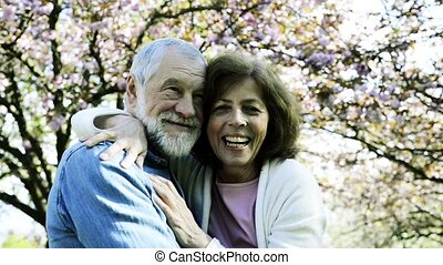 Beautiful senior couple in love outside in spring nature. -...