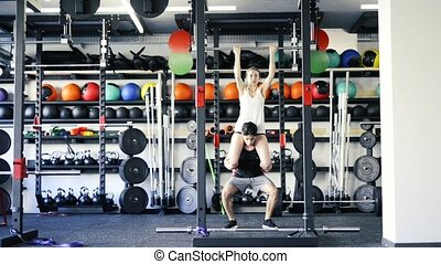 Woman in gym doing pull ups, man giving her piggyback. -...