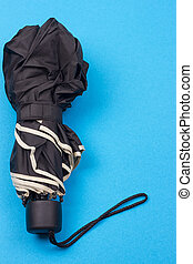 closed black umbrella on the blue background