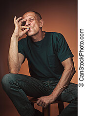 Worried mature man sitting at studio, smoking and thinking...