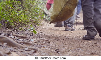 Group of multiracial hikers walking along the forest path. Tourists hiking on footpath through the woods at mountain. Low angle of view Close up