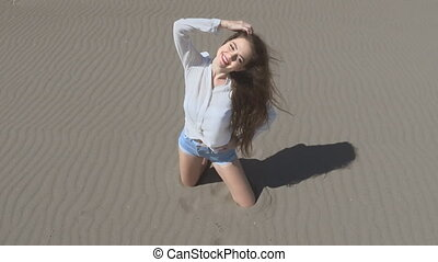 Beautiful young teen woman with blowing hair posing at camera, brunette on beach enjoying life, outdoors slow motion. Summertime vacation
