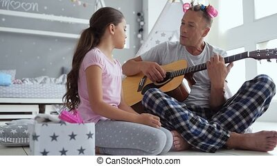 Cheerful cute little girl and her father singing song -...