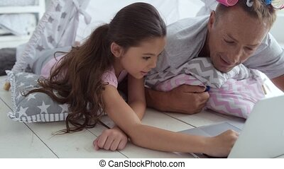 Positive girl and her father surfing the internet
